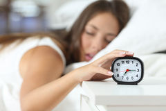 Wake up of an asleep girl stopping alarm clock Royalty Free Stock Photo