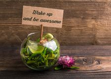 Wake up and be awesome. Text on sign board with flower and leafs on wood Stock Photos