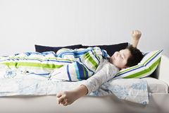 Wake up. Of contented caucasian boy laying down in bed at sunny bedroom stock photo