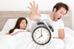 Wake up - couple waking up early throwing alarm Royalty Free Stock Photo