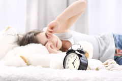 Wake up girl. Girl sleeping on the bed. Rubs her eyes, an alarm clock in the foreground Stock Photos