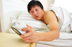 Wake-up late. Shocked young man wake-up in bedroom watch alarm clock Stock Photos