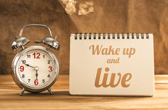 Wake up and live text on notebook with alarm clock on wood table.  stock photo