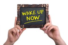 Wake up now sign. A woman holding chalkboard with words wake up now isolated on white background Royalty Free Stock Photography