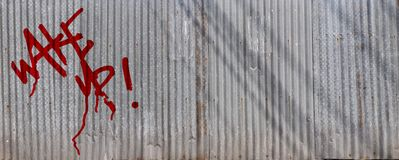 Wake up tag on corrugated zinc fence Royalty Free Stock Photo
