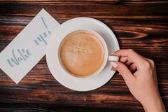 Wake up text. Font of lettering word on white paper by calligrapher. Female hand takes cup of coffee from table. Morning, handwrit royalty free stock photo