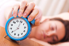 Wake up time. Sleeping woman shuts off an alarm clock - wake up time stock images