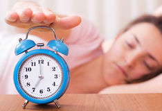 Wake up time. Woman shutting off alarm clock pointing at seven o'clock - wake up time royalty free stock image