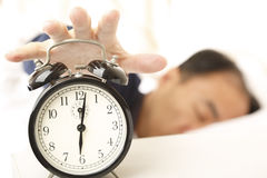Wake-up time. Man in sleep waking up by an alarm royalty free stock images