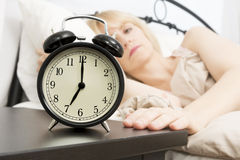 Wake Up Time: Middle Age Woman Reaching for Alarm Clock royalty free stock photography