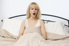 Wake Up Time:  Middle Age Woman Yawns In Bed. A middle age woman yawns as she wake up in morning Royalty Free Stock Images