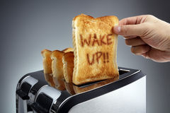 Wake up toasted bread in a toaster royalty free stock image
