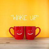 Wake up word.Two cups of coffee and stand together Royalty Free Stock Images