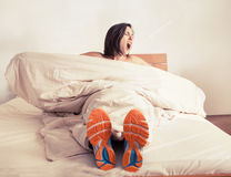Wake up yawning girl in run shoes sitting in bed Royalty Free Stock Photography