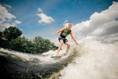 Wakeboard alla moda di guida maschio caucasica sull'alta onda Fotografie Stock