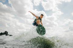 Wakeboard caucasico di guida del surfista sull'alta onda Immagine Stock