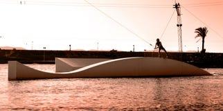 Wakeboard coulissant de sportif de Wakeboarding sur le glisseur dans le wa Photo stock