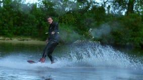 Wakeboard d'équitation d'homme sur la vague de canot automobile Cavalier dans l'embarquement de sillage de formation banque de vidéos
