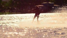 Wakeboard da equitação do homem no por do sol Estilo de vida extremo O cavaleiro aprecia férias extremas filme