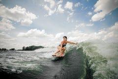 Wakeboard di guida della donna sull'alta onda che spiting fuori spruzzo Immagine Stock