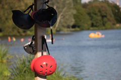 Wakeboard helmets hanging on a pole near the lake.  Stock Photo