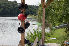 Wakeboard helmets hanging on a pole near the lake.  Royalty Free Stock Photos