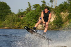 Wakeboard jumper. Young man on a wakeboard jumping out of the water royalty free stock photo