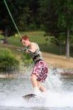 Wakeboard Sport. Teenage boy wakeboarding on the lake royalty free stock image