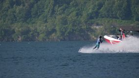 """Wakeboard Woman Jump Motorboat. A girl riding wakeboard on wave of motorboat and jumping the wake during the """"Wake Zone Cup"""" on 1 July 2108 in Lake stock footage"""