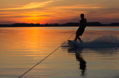 Wakeboarder делая фокусы на заходе солнца Стоковые Фото