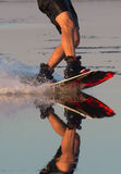Wakeboarder athlete glides through the water with burning spray Royalty Free Stock Photography