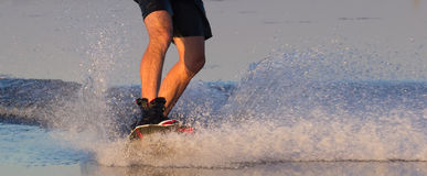 Wakeboarder athlete glides through the water with burning spray Stock Photo