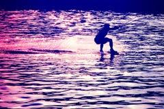 Wakeboarder avant saut dans les rayons du coucher de soleil image libre de droits