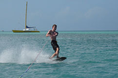 Wakeboarder with Black Swim Trunks Riding Off the Coast of Aruba Stock Photography