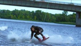 Wakeboarder del atleta que salta alto por encima de la superficie Truco extremo sobre el agua almacen de video