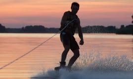 Wakeboarder die trucs op zonsondergang maken Stock Afbeeldingen