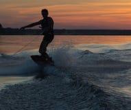 Wakeboarder die trucs op zonsondergang maken Royalty-vrije Stock Afbeelding