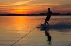 Wakeboarder die trucs op zonsondergang maken Stock Foto's