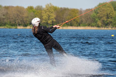 Wakeboarder is doing her trick at Wakeboard track. Royalty Free Stock Images
