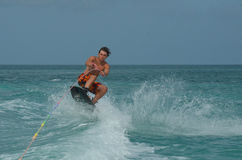 Wakeboarder Doing an Ollie over a Wave in Aruba. Guy wakeboarding and jumping over a wave in Aruba Stock Photo
