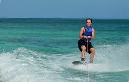 Wakeboarder en un agachar que se prepara para saltar en el aire Foto de archivo
