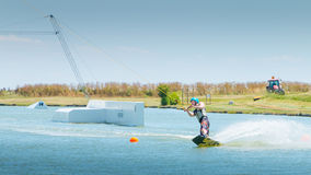 Wakeboarder is exerted on the lake to make figures Stock Images