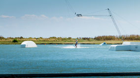 Wakeboarder is exerted on the lake to make figures Stock Photography