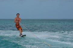 Wakeboarder joven atlético que monta un Wakeboard en Aruba Fotos de archivo