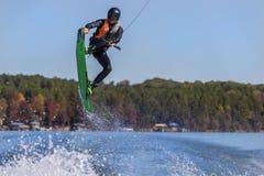Wakeboarder joven que realiza trucos Imagen de archivo libre de regalías