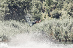 Wakeboarder jump over the lake. Tonned photo. Faded colors Royalty Free Stock Image