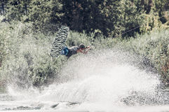 Wakeboarder jump over the lake. Tonned photo Stock Photo