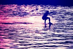 Wakeboarder before jump in rays of setting sun royalty free stock image