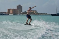 Wakeboarder Jumping Over the Boats Wake in Aruba royalty free stock photo