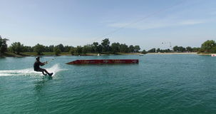 Wakeboarder jumps over the kicker and does a 360 at wake park